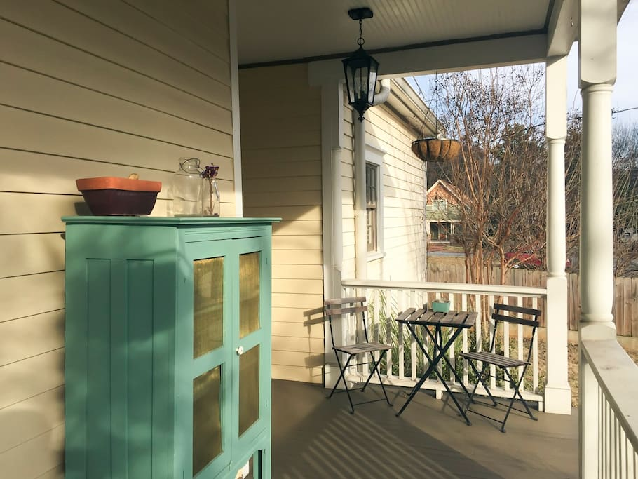 View of pie cabinet and table with chairs on elevated front porch.