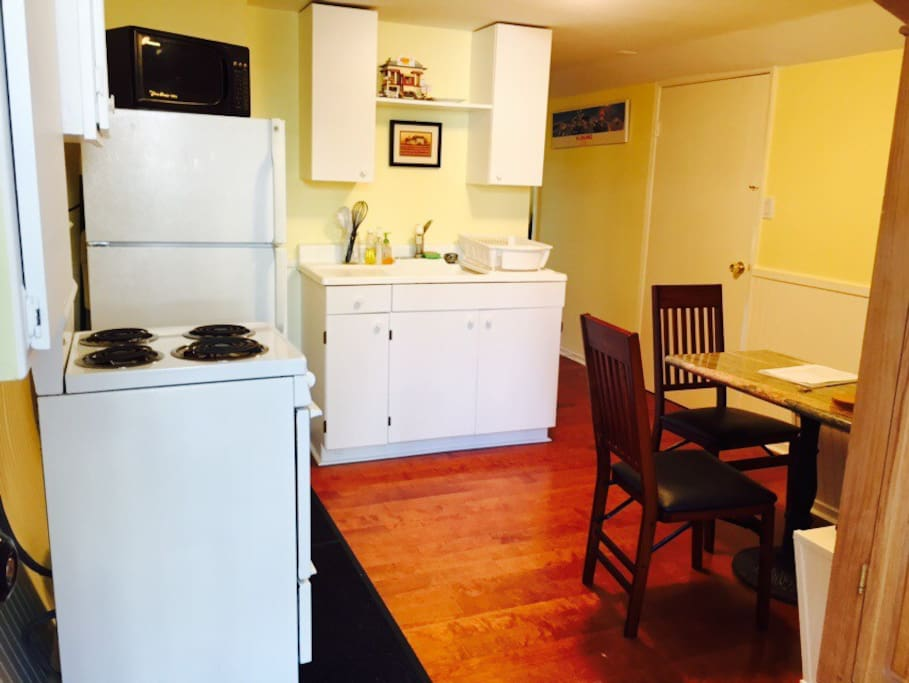 Fully stocked kitchen with stove, refrigerator, pots and pans, cooking utensils and dishes.