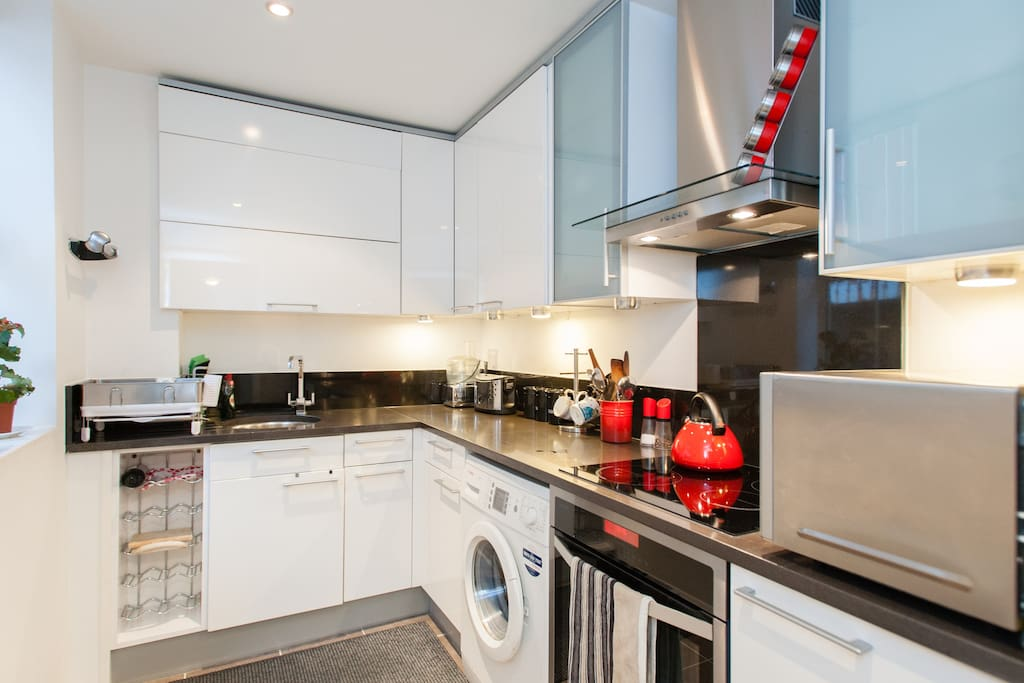 Modern new kitchen with microwave, induction hob, electric oven and washing machine