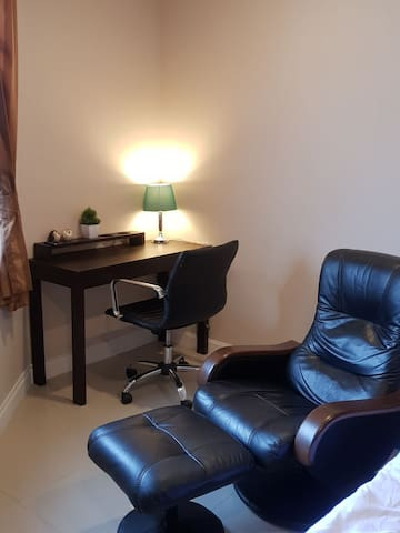 Working desk and recliner chair. You can see Suthep Mountain from window.