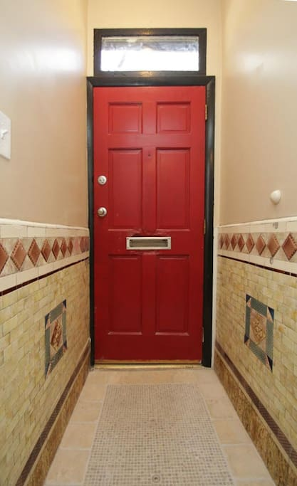 "Who doesn't love a ""red door"" entrance way?   ""The apartment is very well appointed and has a number of entertainment options for music and films. Perfect host, good location easy check in and out. Excellent outdoor space."""
