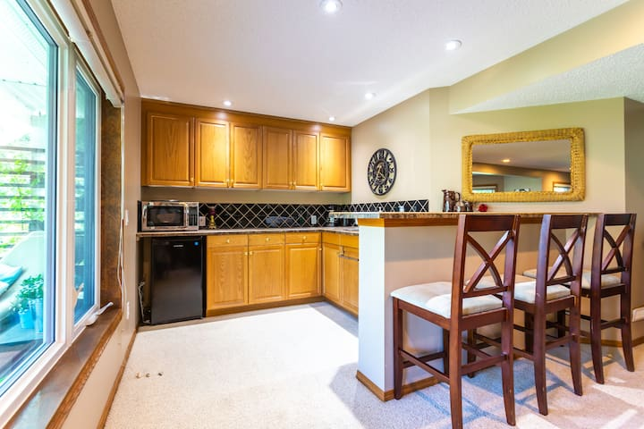 Kitchenette with fridge, microwave, coffee make, toaster and dishwasher.