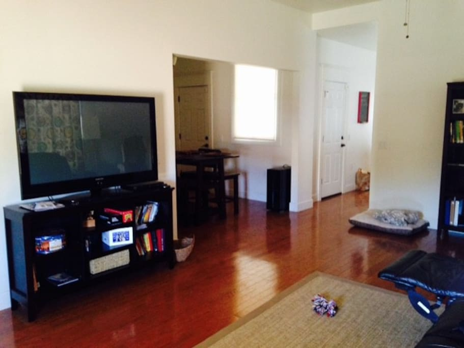 Big screen TV, leather couch, dining room table