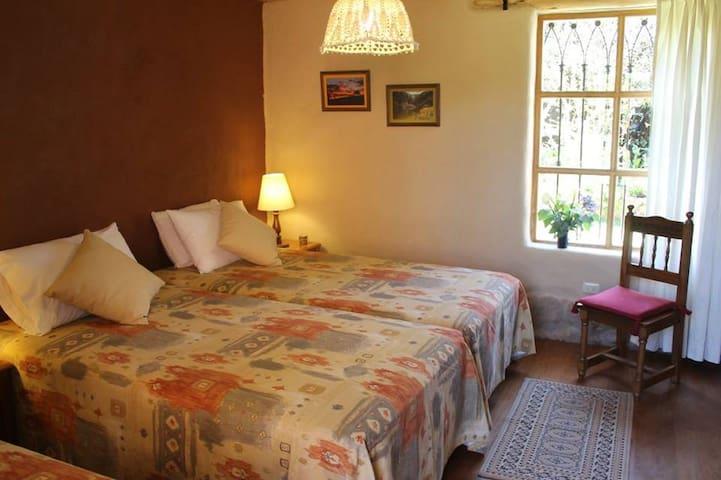 Dormitorio con 03 camas individuales con baño incorporado con ducha.  Bedroom with 03 individual beds  and  bathroom with shower. All beds are extra long (2.05 mt long).  First floor.