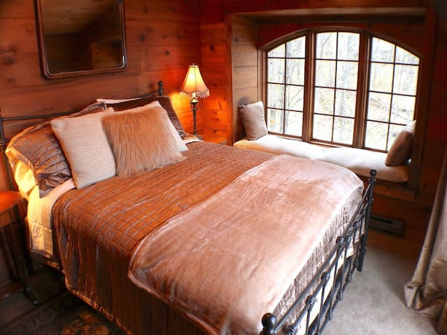 High end linens adorn this master queen bed with supreme views of the lake