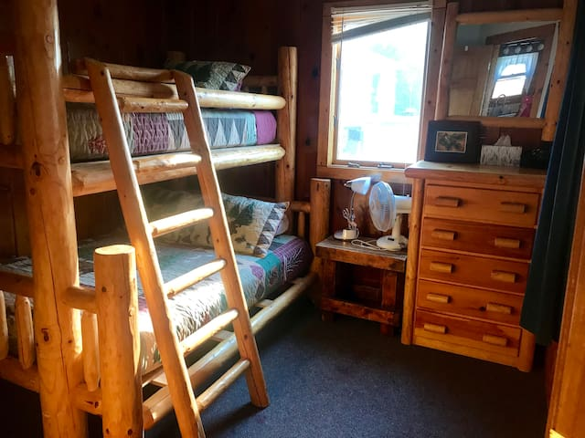 Full/Twin log bunk bedroom with two dressers.