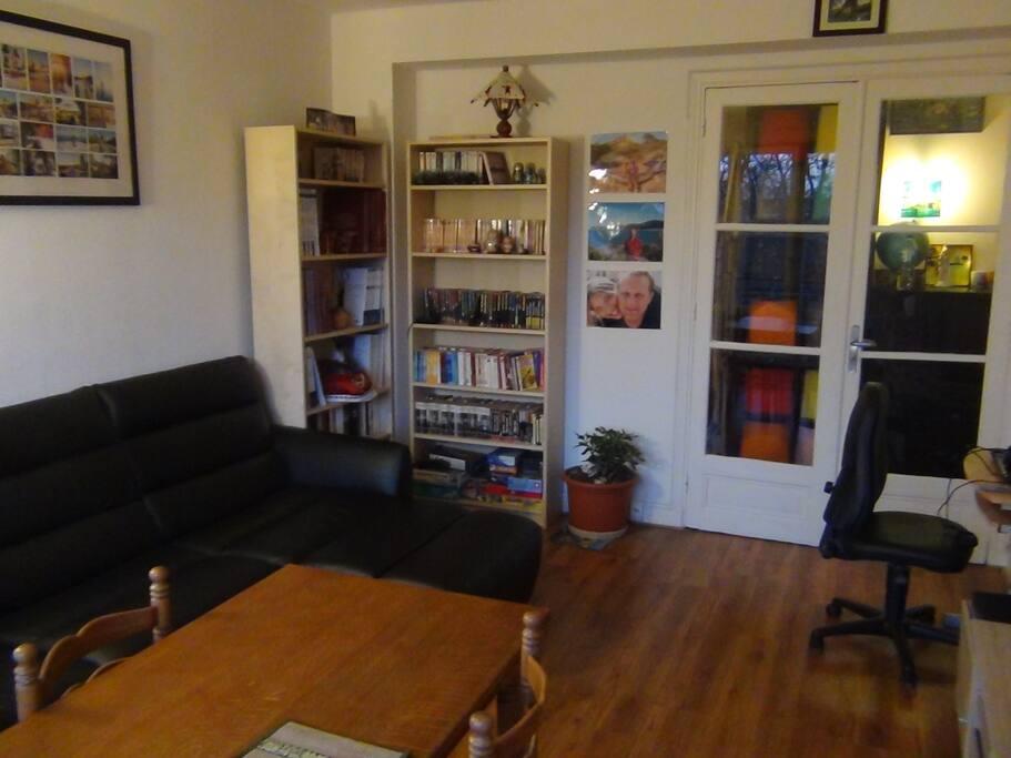 séjour donnant accès au balcon avec canapé confortable, table, bibliothèque, jeux de société, espace de travail