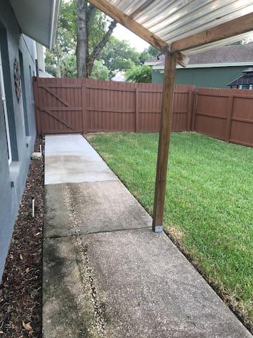 Sidewalk, side yard & entry to apartment