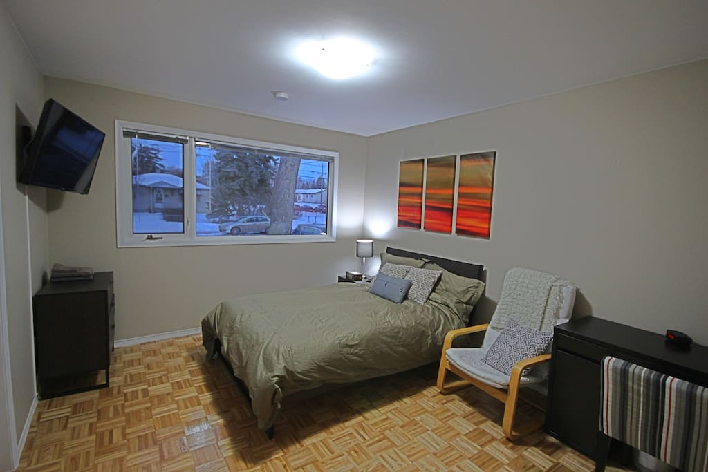 One of two bedrooms. The room includes a double bed, wall mounted television, dresser  and desk.