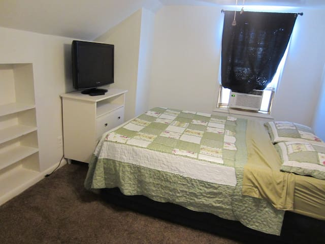 Guest room from the doorway. Bookshelves hold two clean towels and two clean washcloths.