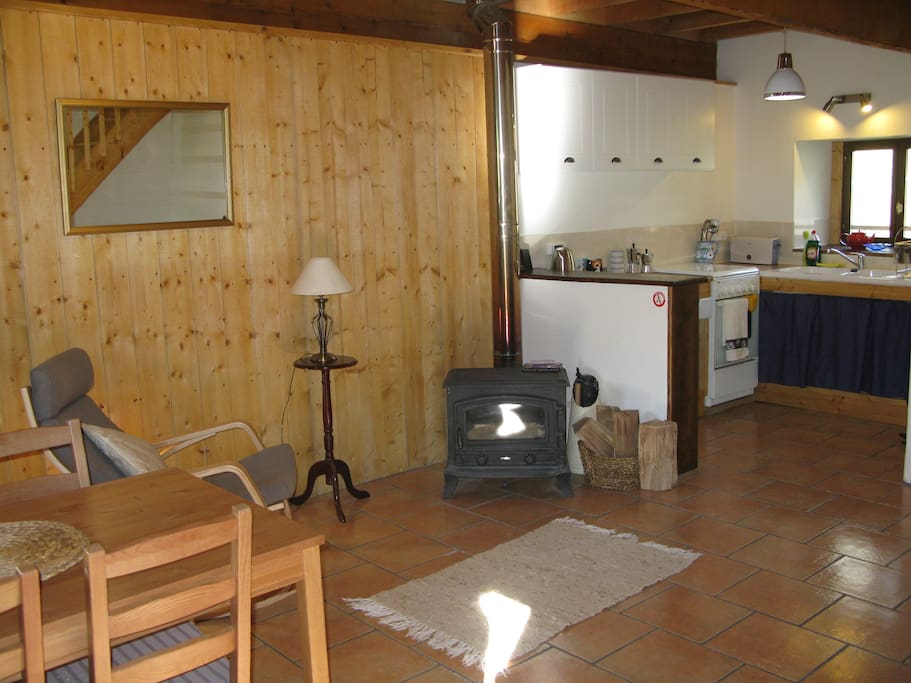 The lounge, dining and kitchen are downstairs. The log burner is a great place to relax in front of on a chilly night