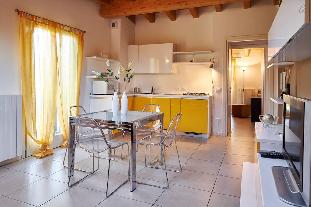 Grande soggiorno luminoso con balcone e tavolo di cristallo , tutta la casa ha le trave a vista