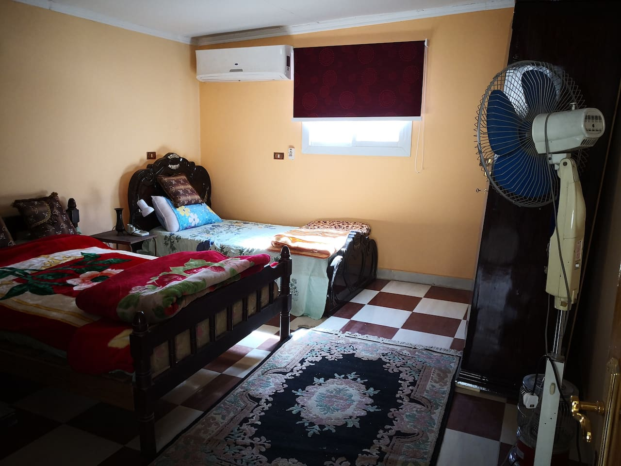 Bedroom with 2 beds and split air conditioner, 2 closet, desk, big TV, stand fan
