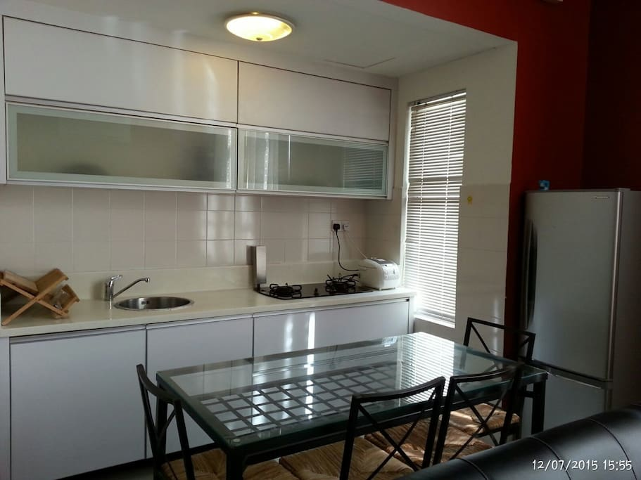 Kitchen with cabinet, refrigerator, dining table & chairs