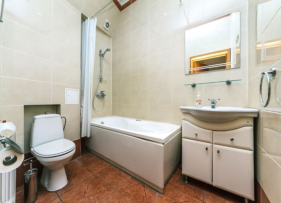 Clean and light bathroom consists of bath tub, toilet and wash basin with mirror. Hairdryer and towels provided.