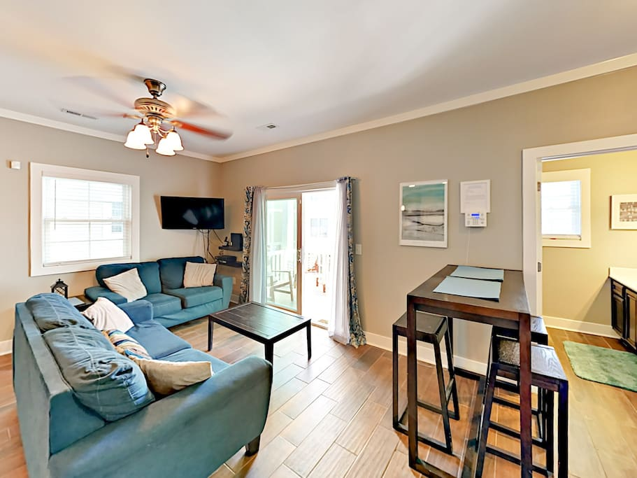 Open-concept living room welcomes with a pretty blue couch and love seat set and cafe table for 4.