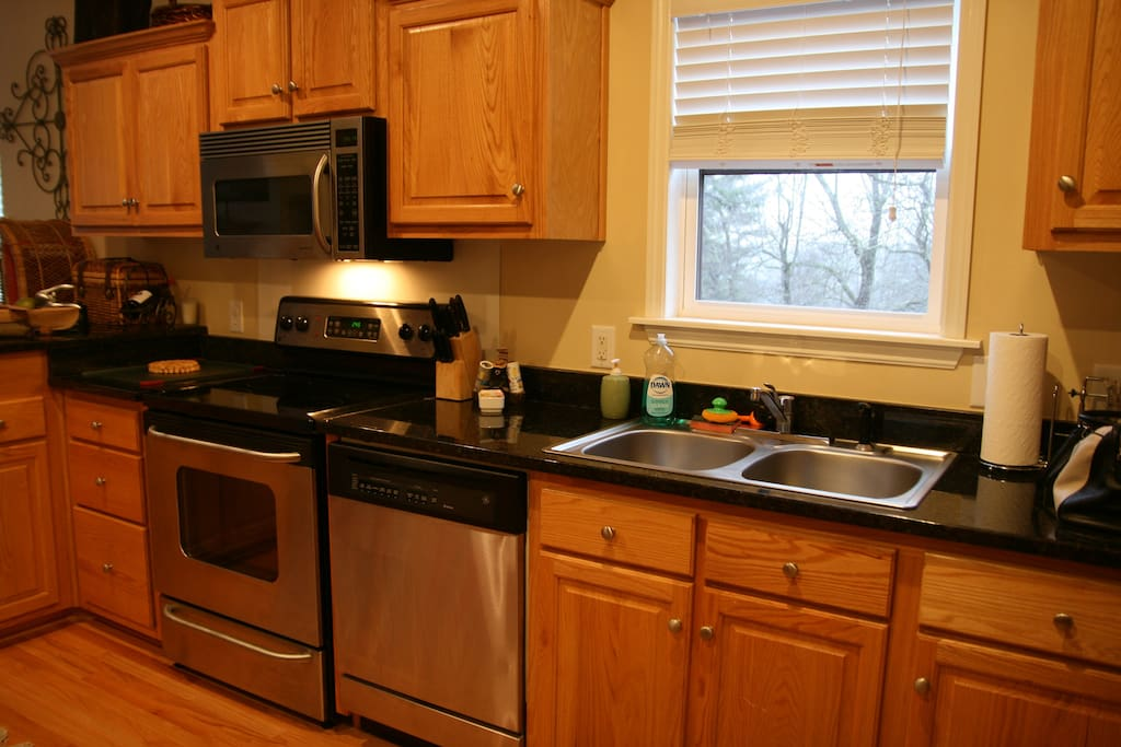 The kitchen is equipped with a 4 burner stove with oven, microwave, dishwasher and refrigerator and freezer.