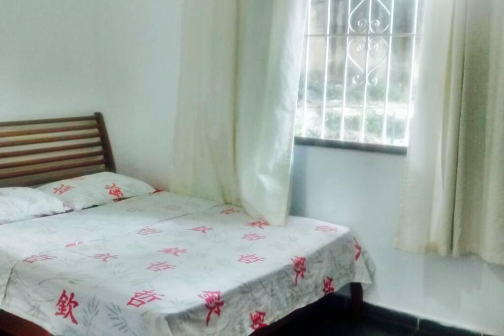Quarto com grande cama de casal e janela com vista para o Cristo