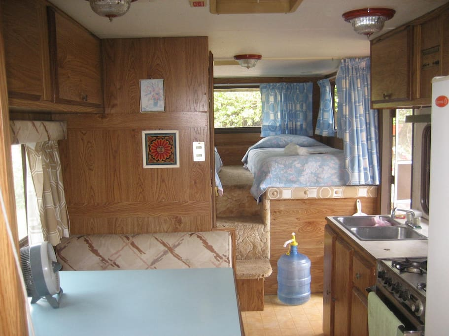 Interior view shows the kitchen and two single beds