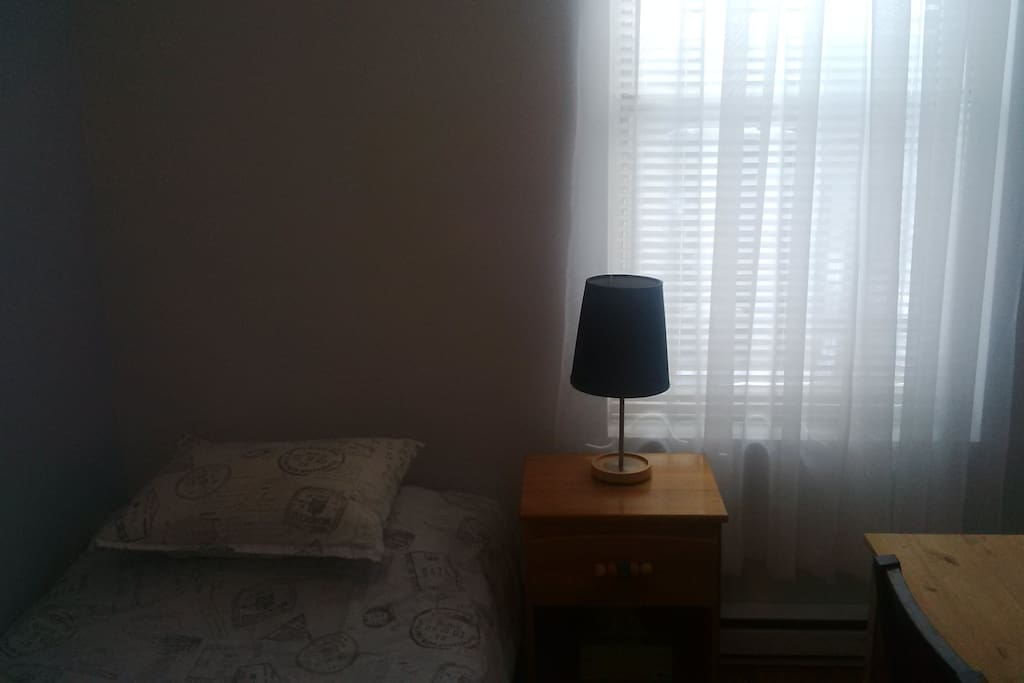 Single bed and large window in room