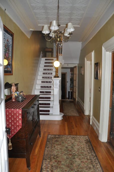 Entryway with press-tin ceiling, antique newel post lamp, and pump-organ.