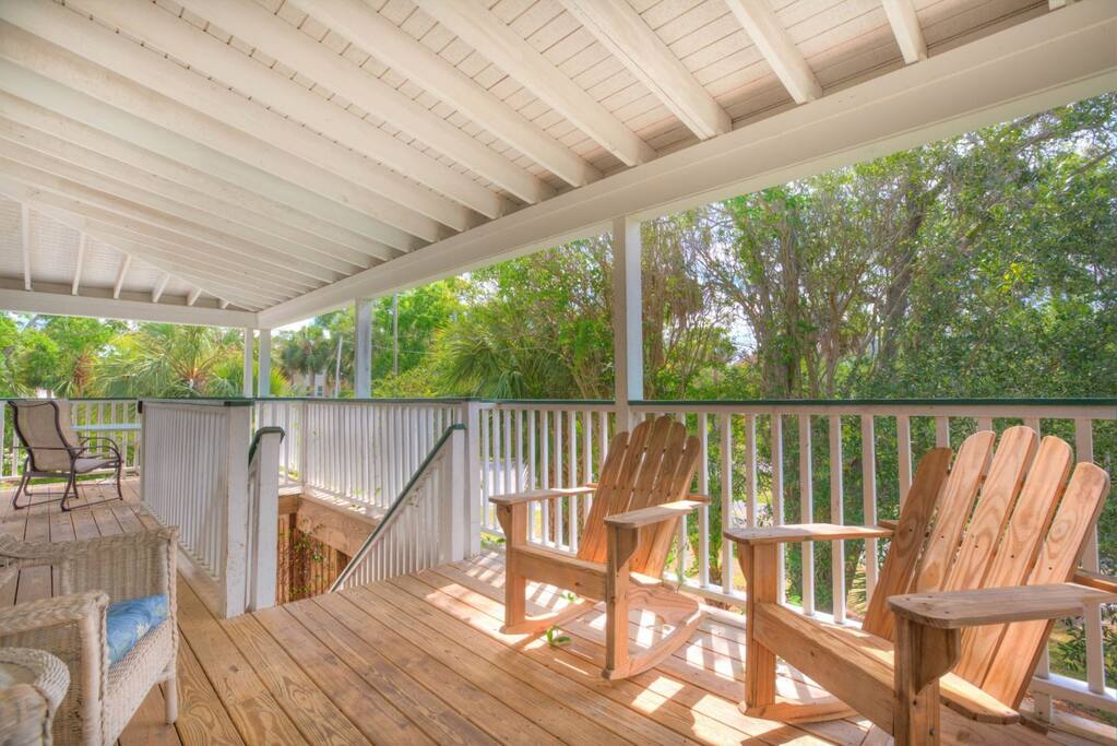 Large screened balcony area with plenty of comfortable seating.