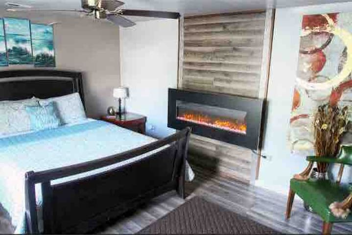 Master has big screen tv, Bluetooth alarm clock radio with outlets and usb. Electric fireplace has remote that changes color of the flames. Use as a heater or just for lighting effects. Cozy seating area.