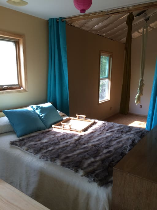 Curtains next to the platform queen bed open to the aerial gym