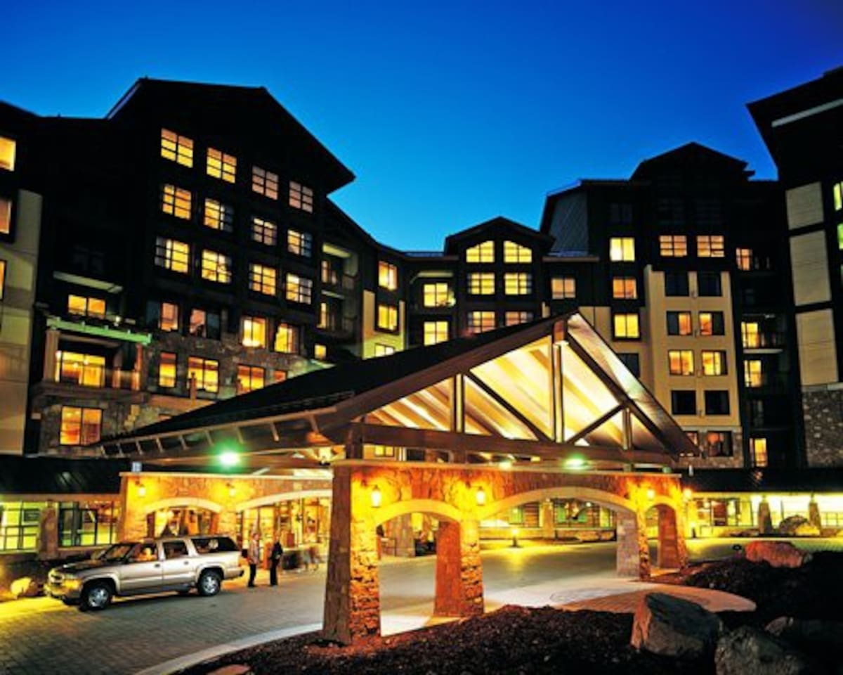An exterior view of multi story resort units at night.
