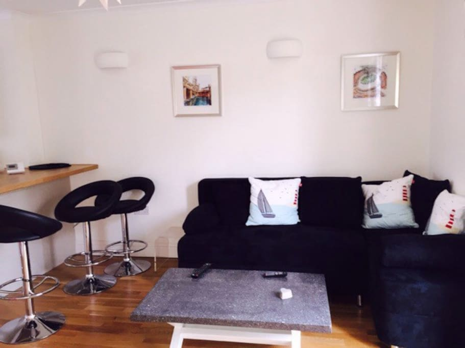 Living area with breakfast bar. Property is centrally heated. Living room has T.V. on wall and wifi is available also.