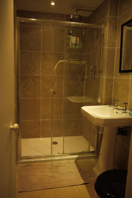 Bathroom with Power shower, sink and lavatory.