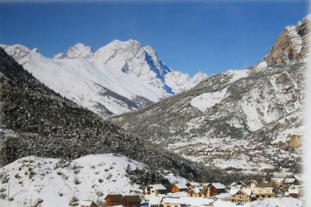 Une vue d'ensemble de la vallée et du massif des Ecrins. On voit le chalet au premier plan du petit hameau.