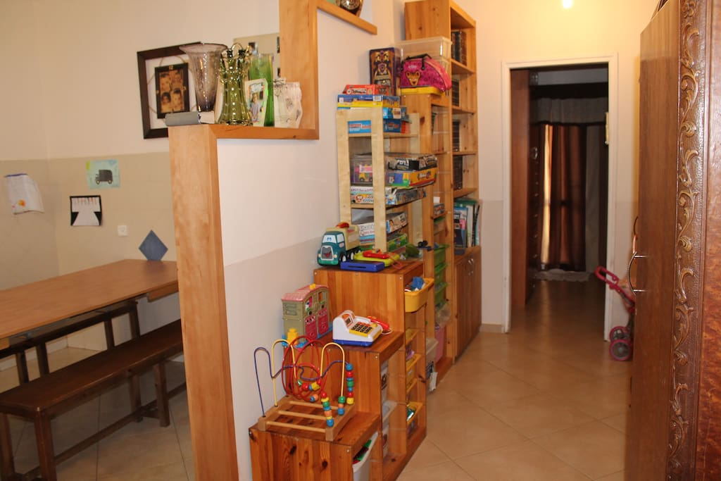 A half wall separates the dinette area from a well equipped toy room.