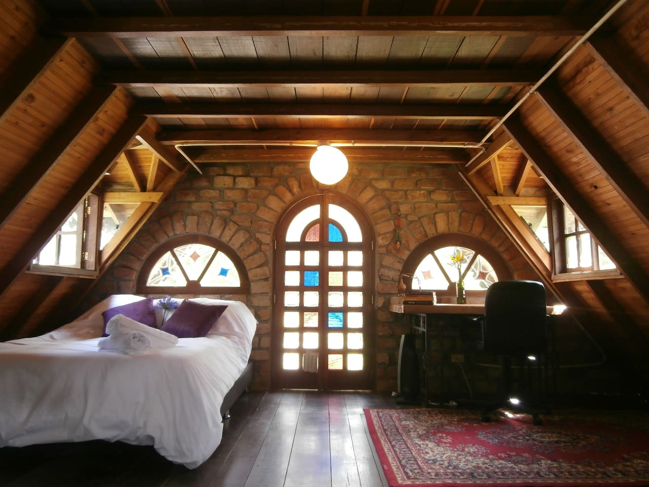 The Gingerbread House's bedroom with stained glass windows, views over the mountains, a wonderful work space, comfy bed and large balcony looking over the front yard