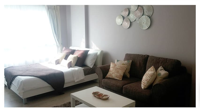 Living and bedroom area, two seater sofa and queen size bed