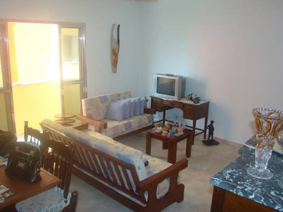 Sala de estar com varanda, TV, Wi-Fi, ventilador de teto.