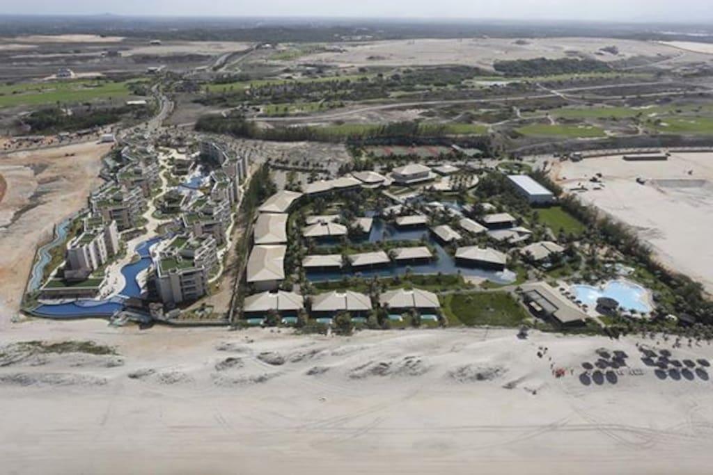 Foto aérea com a Vista aérea do condomínio Riviera Beach Place e a direita o resort D.  Pedro Laguna