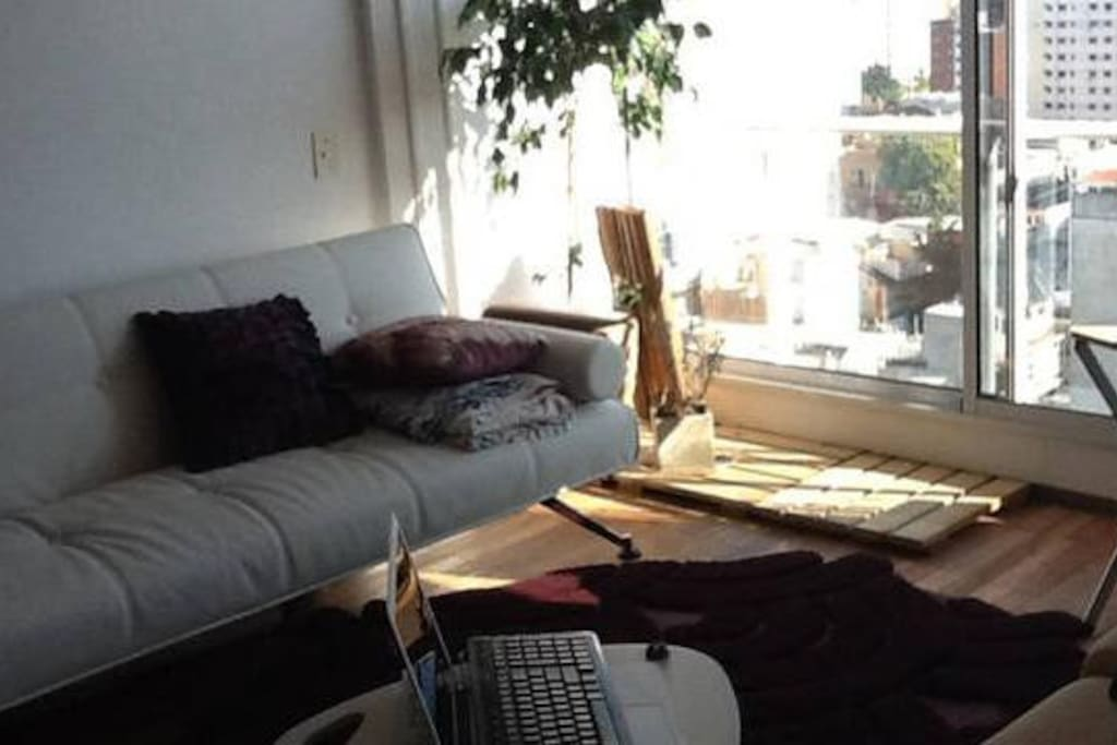 Sun-drenched living room with sofabed- Living soleado con sillón cama