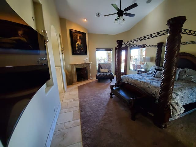 Master bedroom fireplace and chaise. Access to back patio.