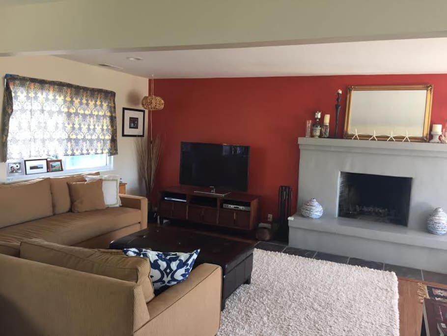 Upstairs living room with large couch, ocean views, working fireplace, and flat screen TV and entertainment center.