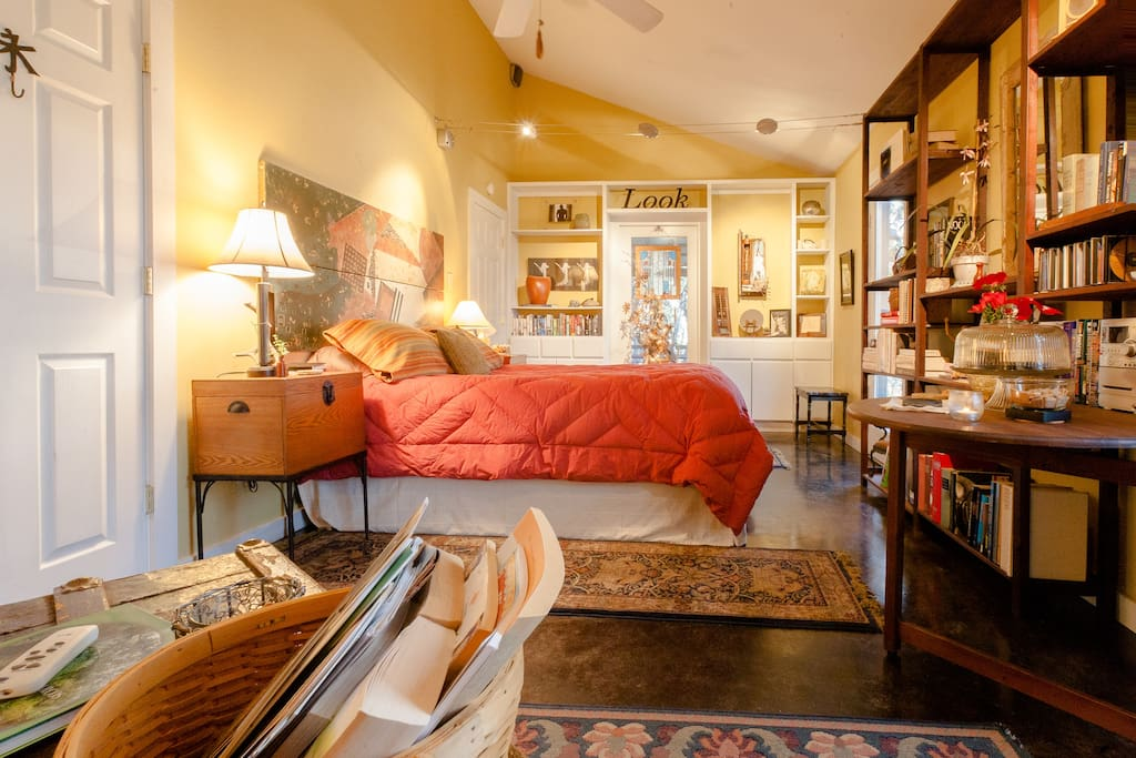 Queen bedroom, featuring beautiful tree-top view, great art, and more books!