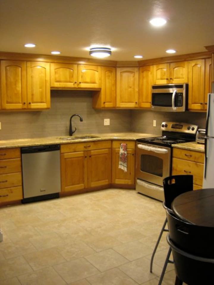 Spacious Kitchen with new appliances, granite counters, undercabinet lighting, pots and pans and most any thing.