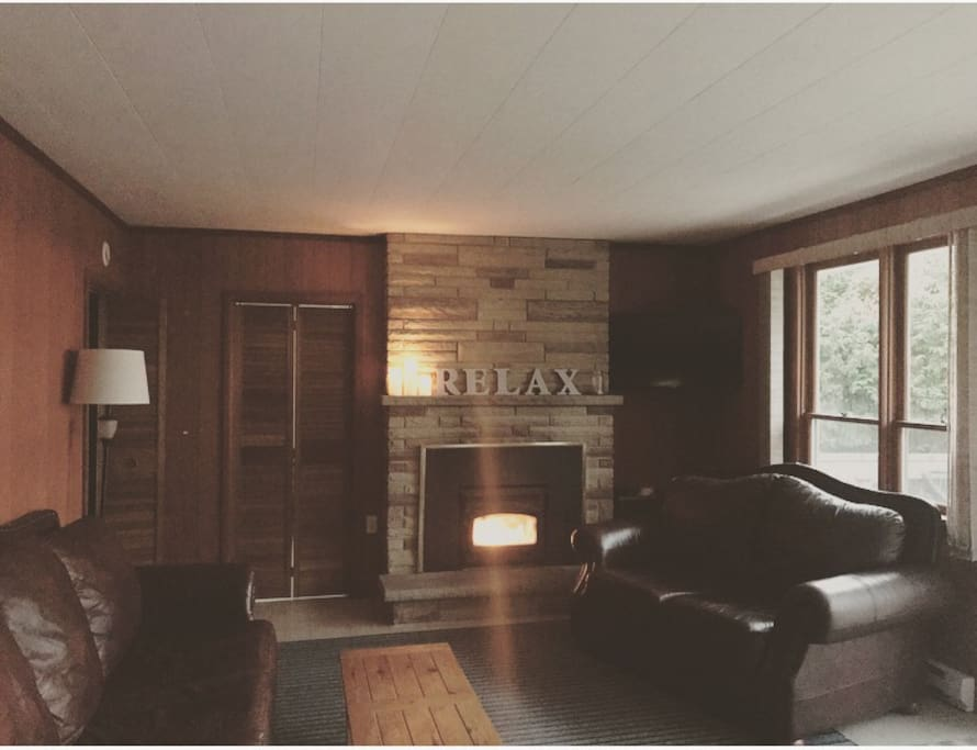 Relaxation is easy here! Tv mounted in the corner. Wood burning fireplace and electric baseboards for keeping things cozy in cooler months.