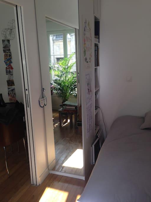 La chambre avec la porte coulissante et le salon