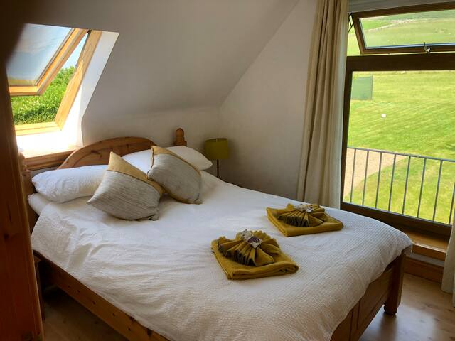 Bright dual aspect bedroom with double bed over looking Rhossili down to the rear and Carmarthen bay to the west from the velux.