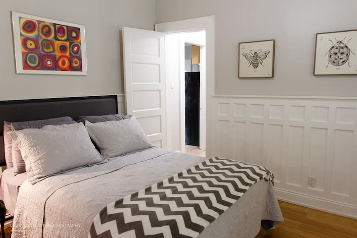 The first bedroom has a queen sized bed, storage for luggage, and a smart TV.