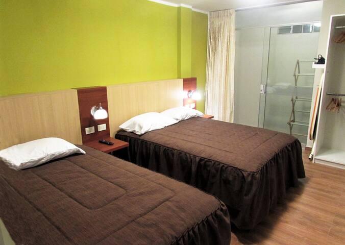 El dormitorio del departamento cuenta con 2 camas: 1 de 2 plazas y 1 de 1 1/2 plazas, veladores de melamine con tomacorrientes para enchufes de Perú y Chile e interruptor de conmutación, secadora, planchador, closet y TV-cable con Netflix.