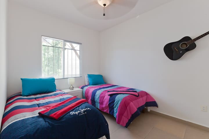 The secondary bedroom with 2 single beds and big ceiling fan.