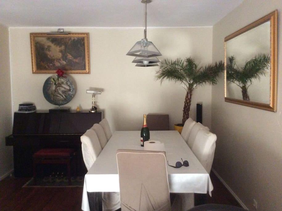 Salon vue sur le piano , la table de repas et le miroir
