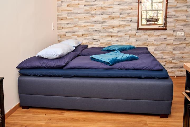 Boxspringsofa ausgezogen zum Bett. Mit extra Topper für Hygiene und Komfort